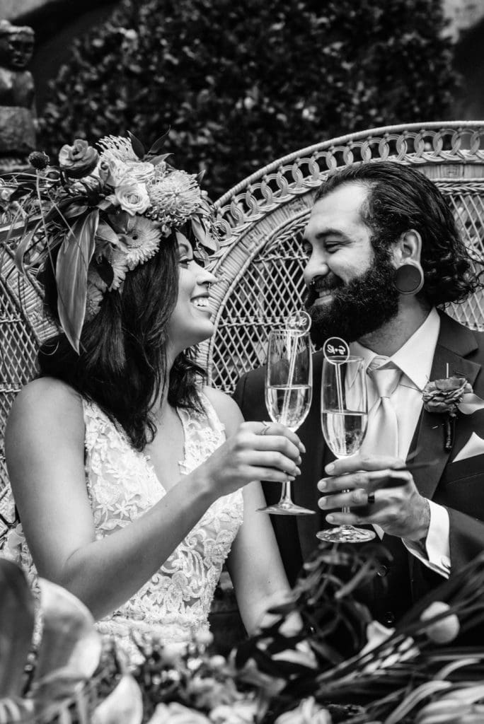 Bride and Groom enjoy a laugh and a drink as they look at each other during their wedding reception