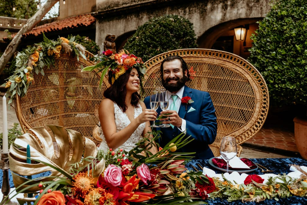 Wedding couple laughing at their tropical flower covered sweetheart table in Sedona, Arizona