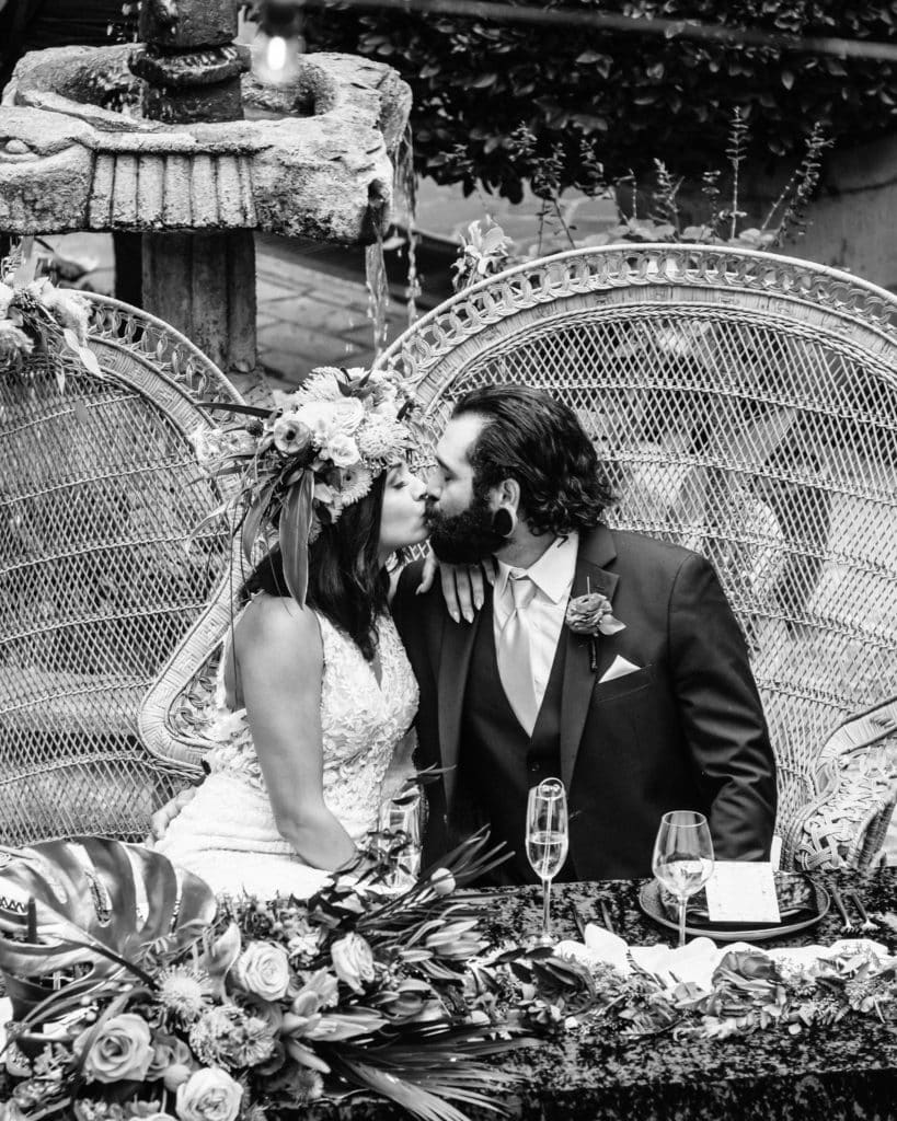 Bride and groom kiss with Tlaquepaque courtyard fountain seen behind their sweetheart table
