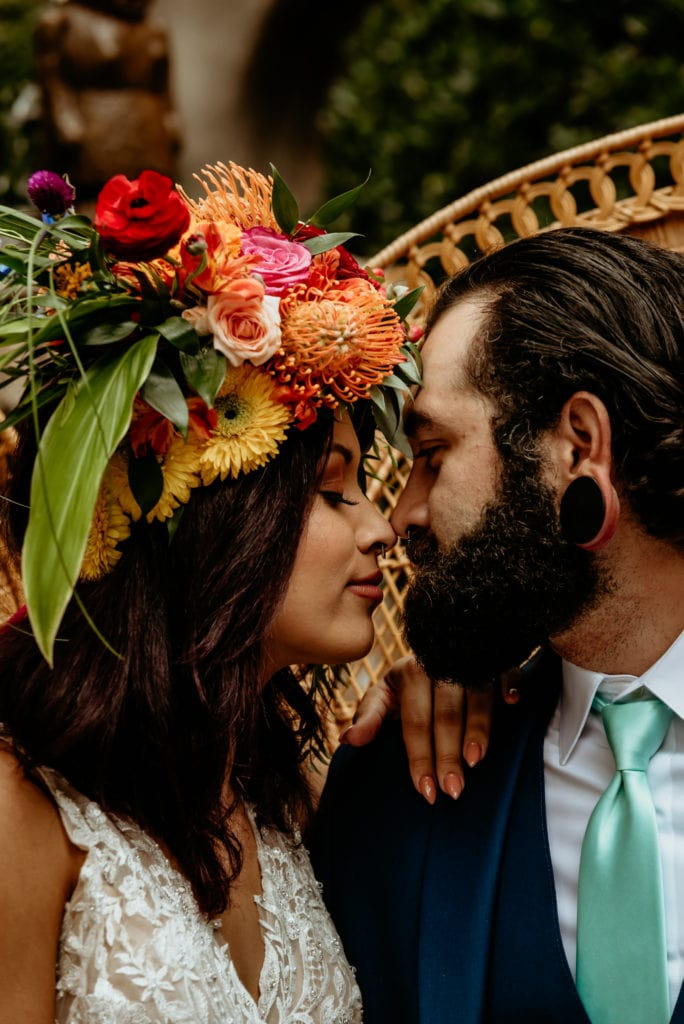 Intimate moment between bride and groom showing brides colorful flower crown with red, orange, yellow, and pink tropical flowers