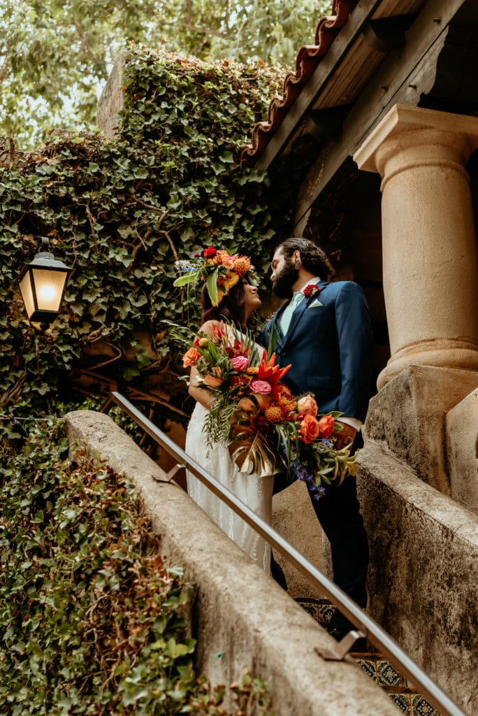 Bride and groom surrounded by ivy covered stucco walls in the Tlaquepaque courtyard