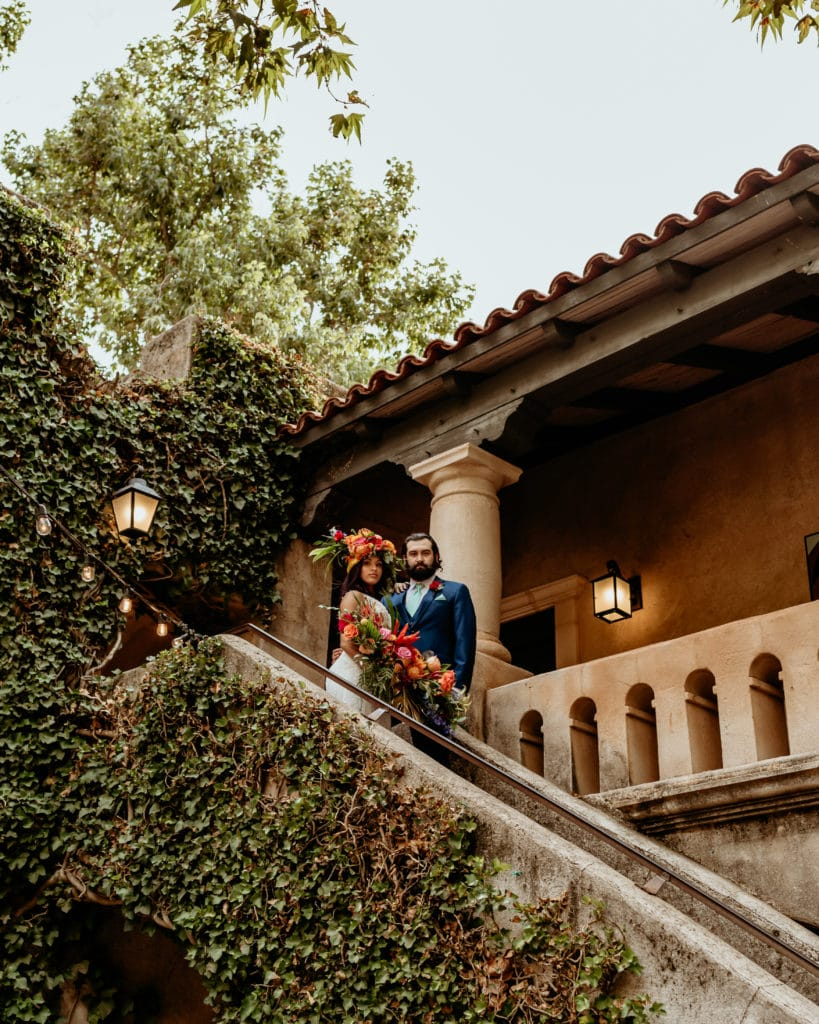 Tropical goddess bride and groom at the top of ivy lined stairs overlooking a stucco courtyard