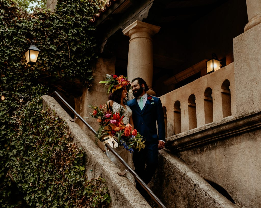Deep green vines on the walls around bride and groom as they descend the stairs