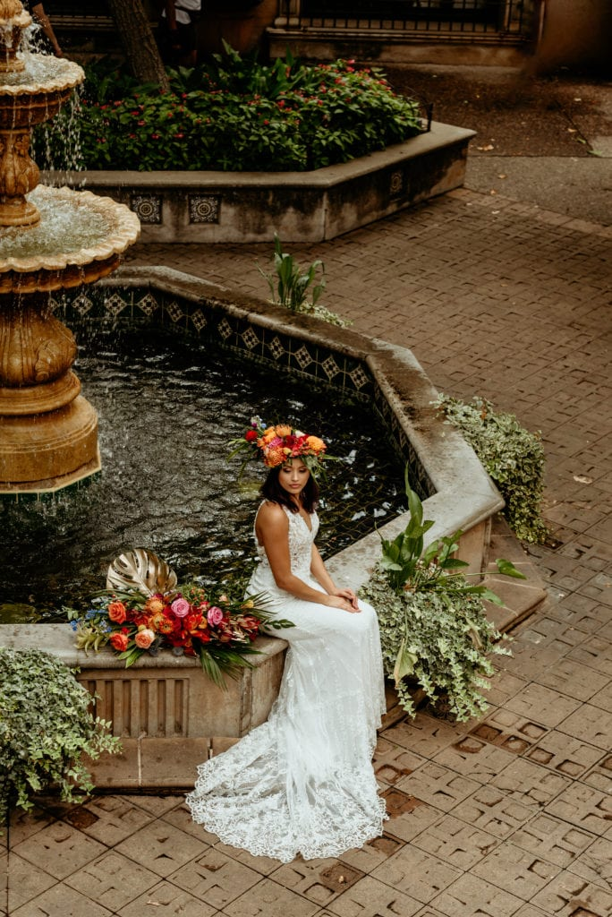 Tropical bride seated at deep blue fountain in Tlaquepaque