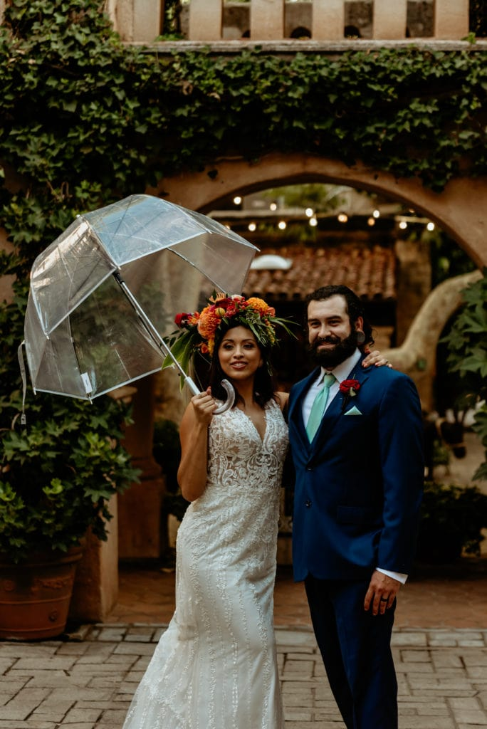 Bride and groom smiling in the light rain at Tlaquepaque in Sedona
