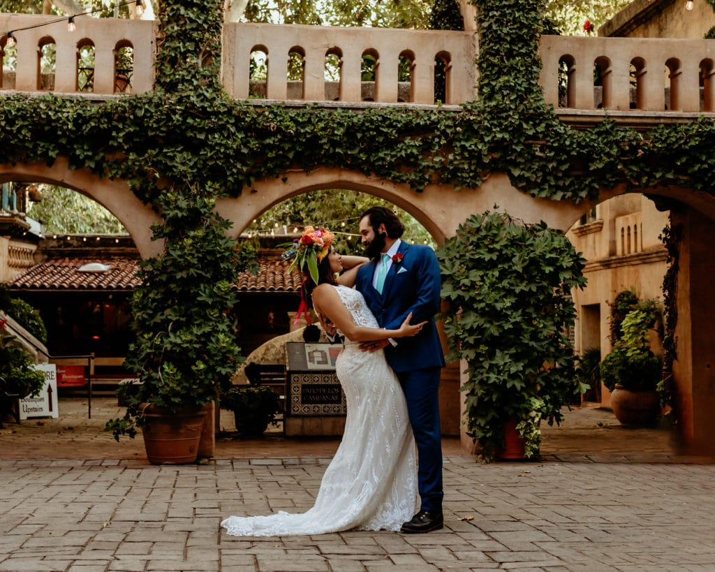 Groom dipping bride in ivy lined courtyard at Tlaquepaque in Sedona