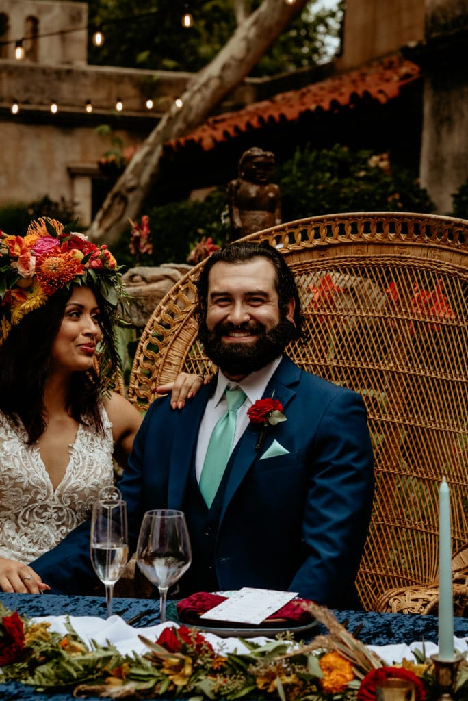 Groom laughing as bride with tropical headdress looks at him lovingly in courtyard wedding