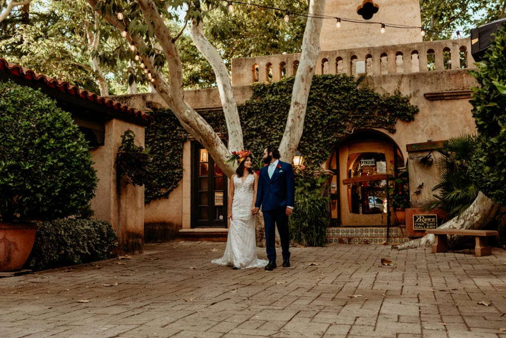 Elopement couple walking hand in hand through a tree lined courtyard