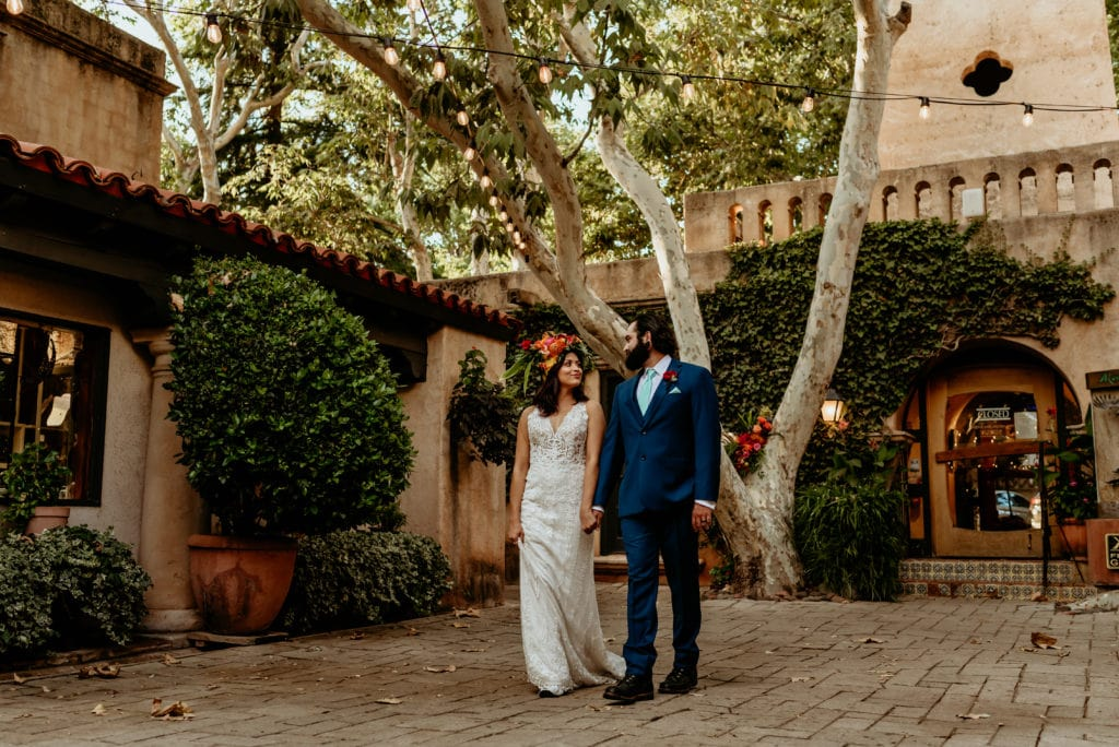 Bride and groom stepping through the shaded courtyard