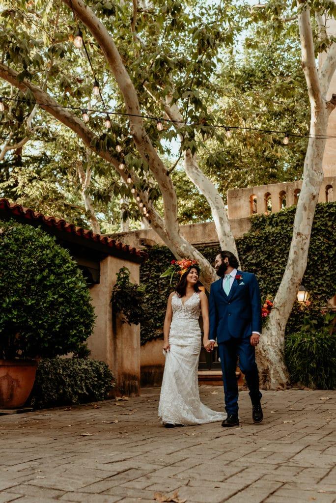 Bride and groom walking hand in hand in the courtyard of Tlaquepaque