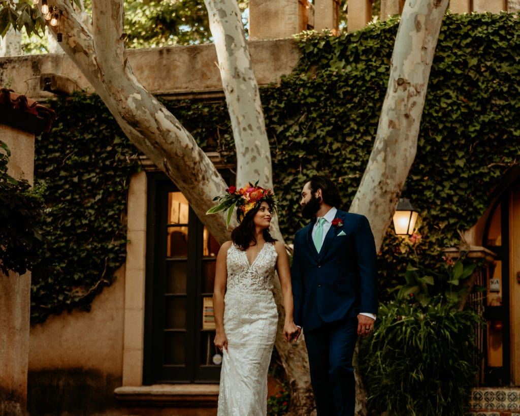 Bride in long lace gown as she gazes at her husband in the courtyard