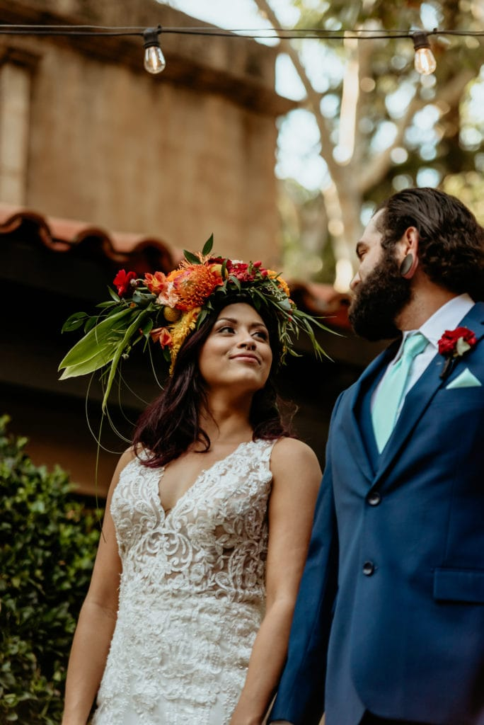 Bride smiling at her groom wearing a navy blue suit