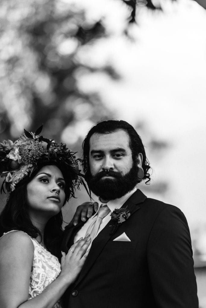 Black and white photo of groom staring into camer