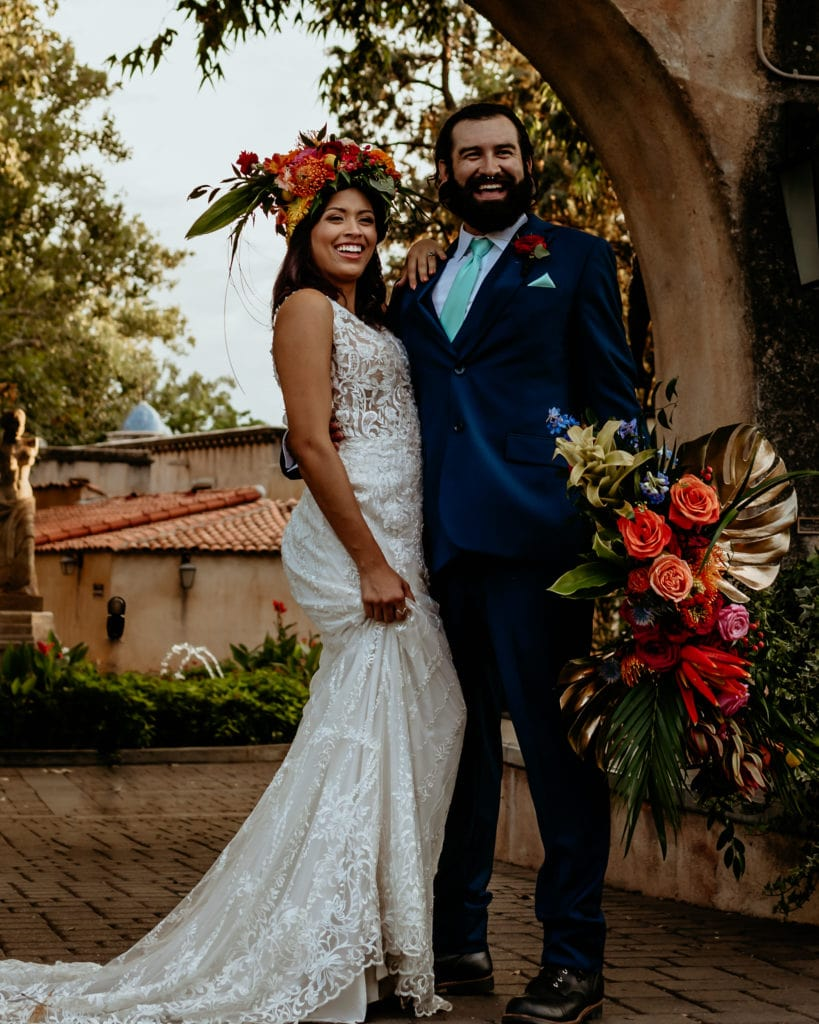 Wedding couple laughing in front of the main Tlaquepaque entrance