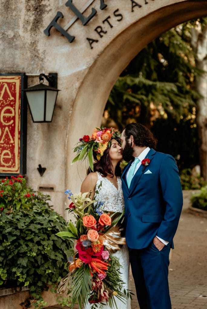 Groom kissing bride holding massive tropical bouquet and headdress