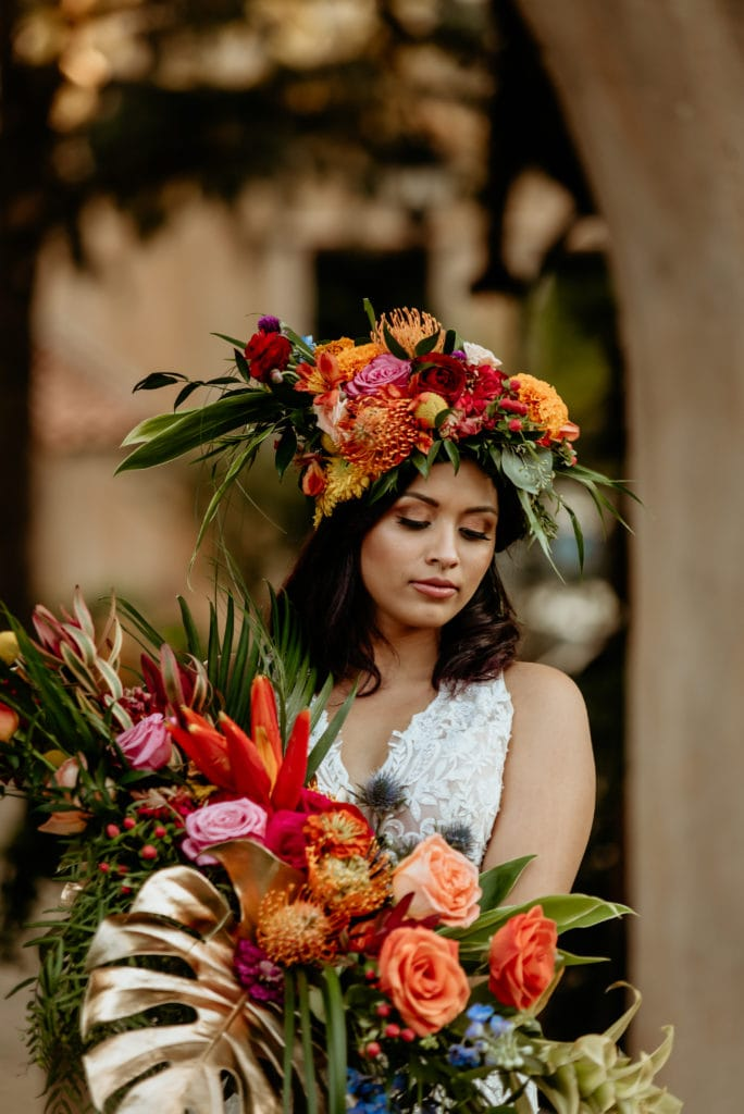 Bride looking down at her colorful tropical bouquet
