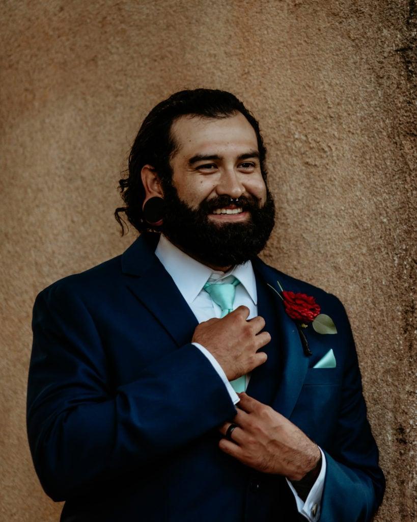 Groom smiling as he adjusts his tie