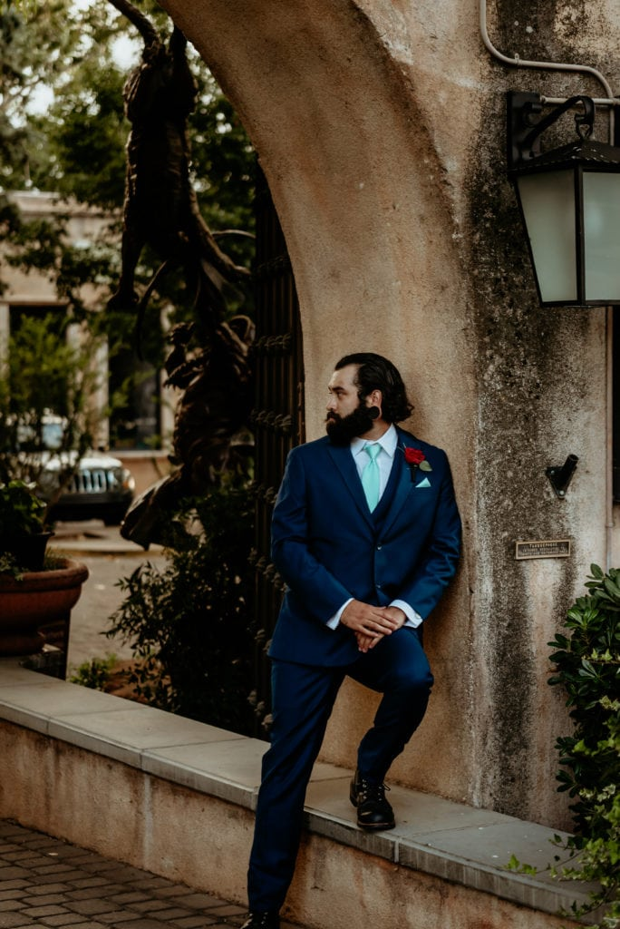 Groom in navy blue suit and teal tie leaning against stucco wall