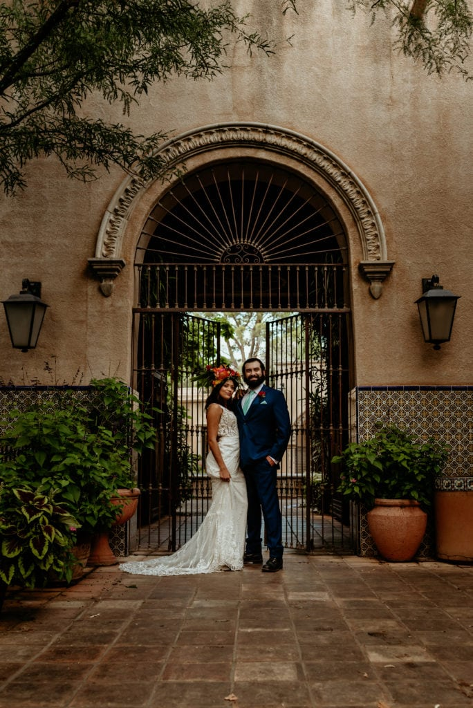Bride and groom portrait in front of Spanish gates and tiled walls