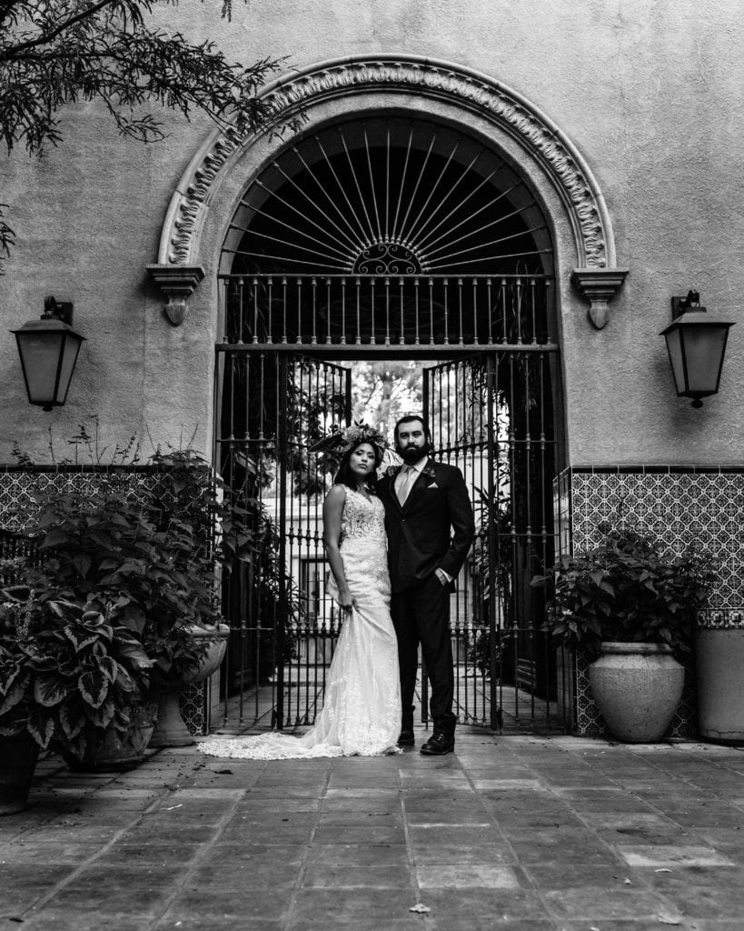 Black and white of bride and groom in front of gate at Tlaquepaque arts and crafts village