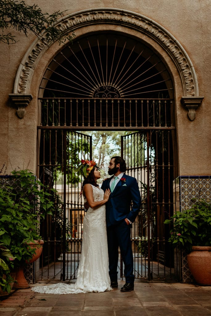 Wrought iron gate towering behind wedding couple