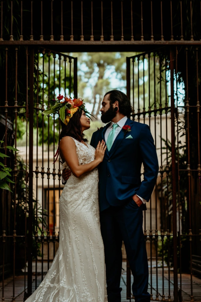 Bride and groom gazing into each others eyes in front of wrought iron gates