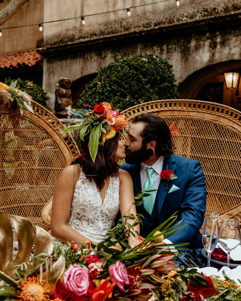 Couple kiss at their sweetheart table seated in wicker peacock chairs