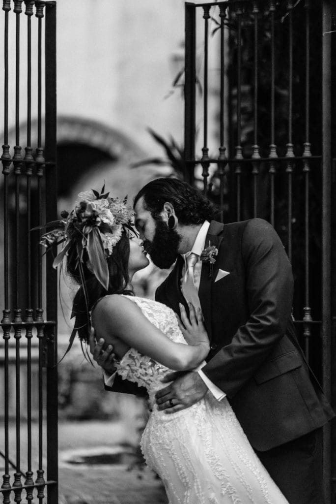 Black and white portrait of groom dipping bride into a kiss