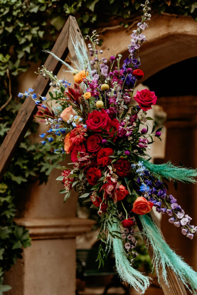 Gorgeous ceremony arch with deep reds, bright purple, orange, yellows, and sprigs of teal