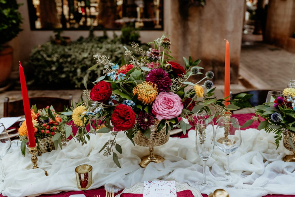 Beautiful vibrant floral arrangements on reception table in Tlaquepaque courtyard