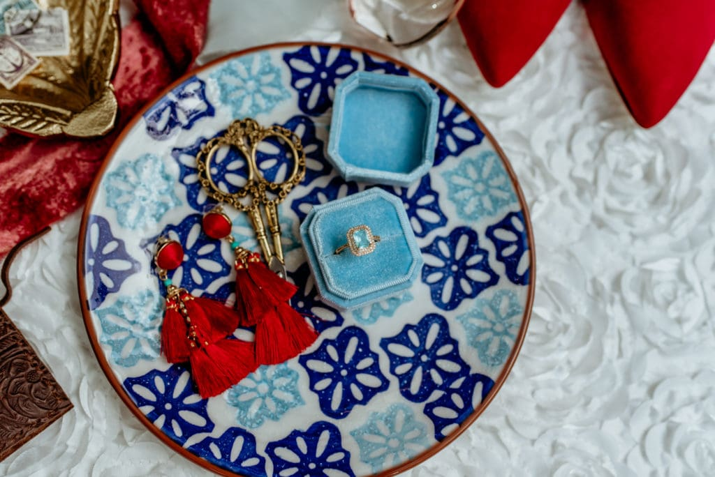 Beautiful blue and white Spanish tile clay plate with engagement ring and bright red tassel earings