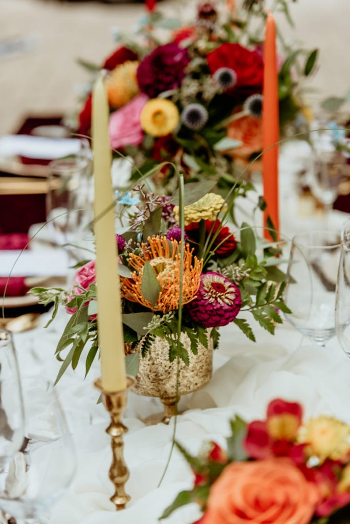 Floral center pieces flanked by colorful candles during a Tlaquepaque wedding reception
