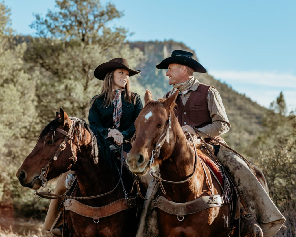 Couple in ranch clothing smiling at each other as they ride their horses side by side