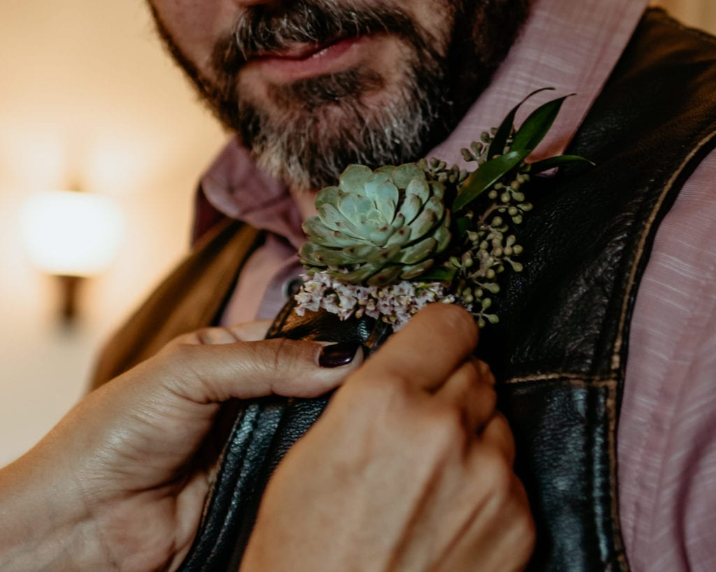 Succulent boutonniere being pinned on grooms leather vest