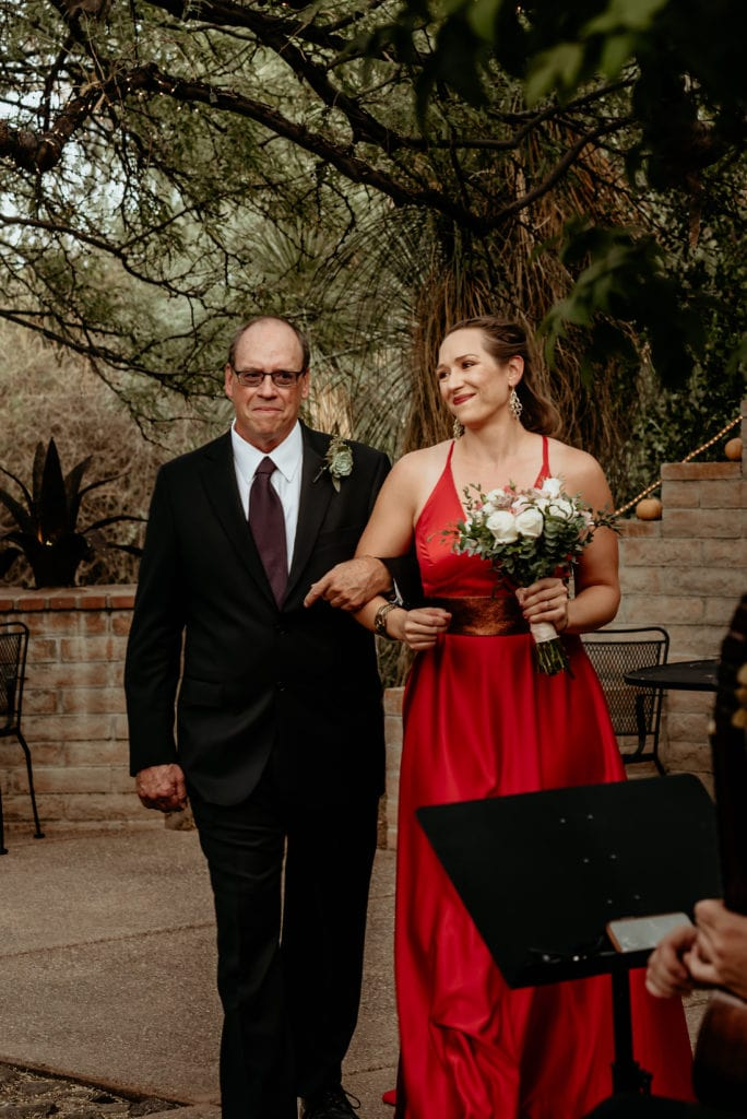 Bride walking down the isle in her bright red dress
