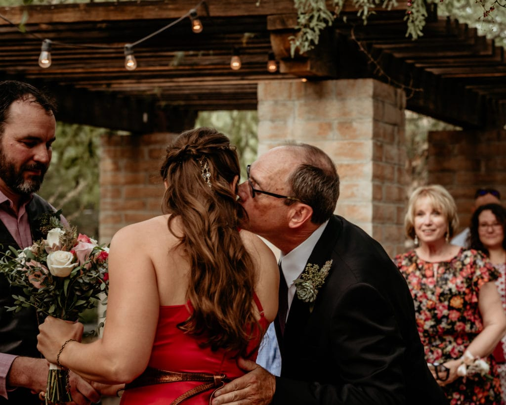 Father kissing bride after waking her down the isle