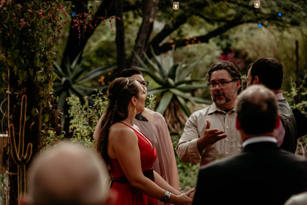 Bride listening to officiant with the lush desert greenery behind them