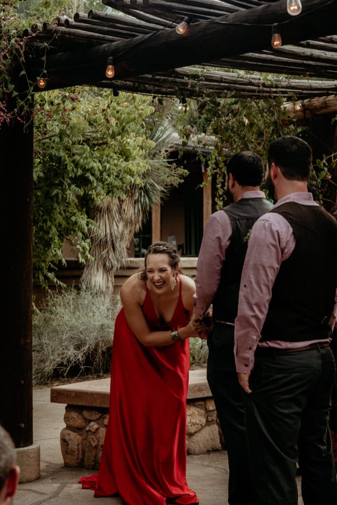 Bride laughing in her vibrant red wedding dress
