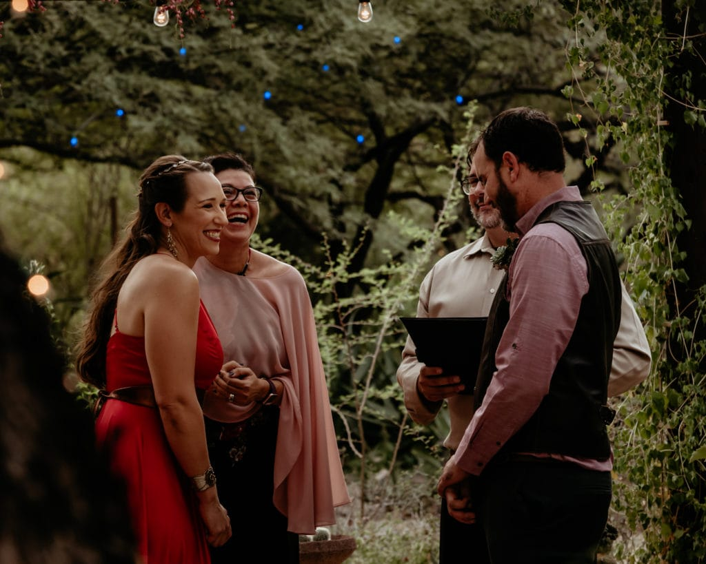 Non-traditional wedding couple in red dress and leather vest at Tucson Botanical Gardens wedding