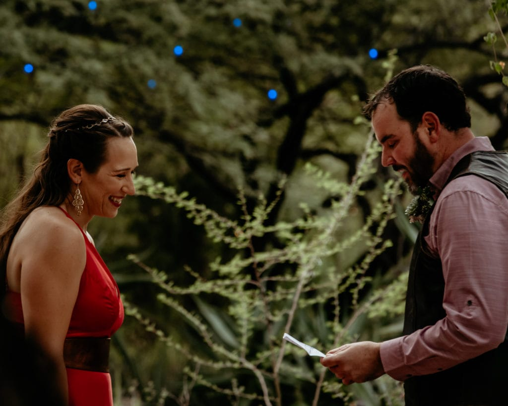 Groom reading his vows to wife surrounded by trees and vines at Tucson Botanical Gardens wedding
