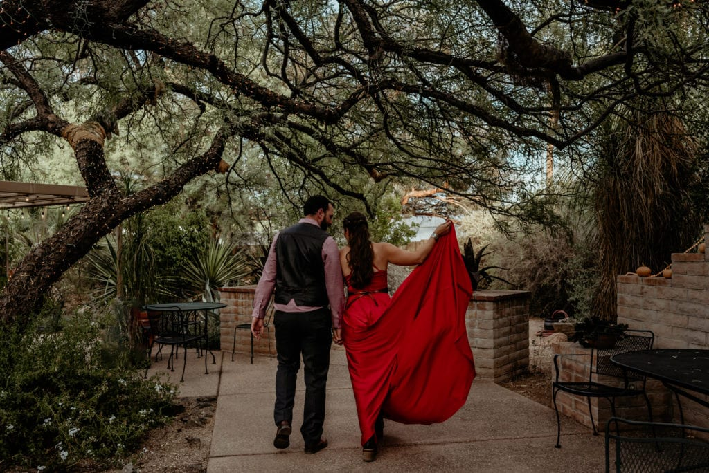 Bride holding the train of her fire red dress as couple walks away